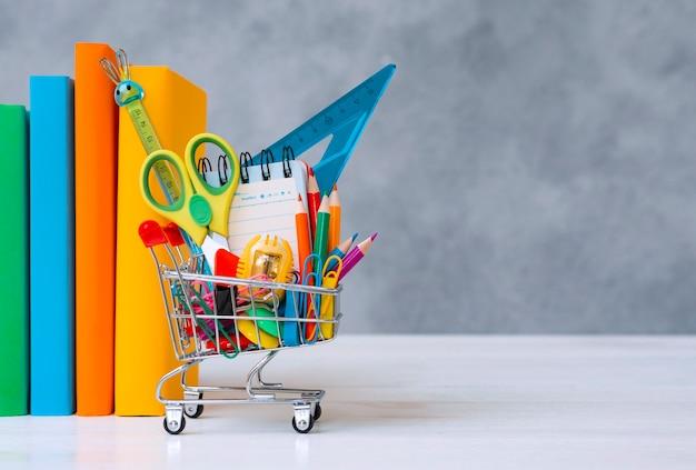 Material escolar colorido na cesta de compras em um fundo cinza com uma cópia do espaço de texto a ...