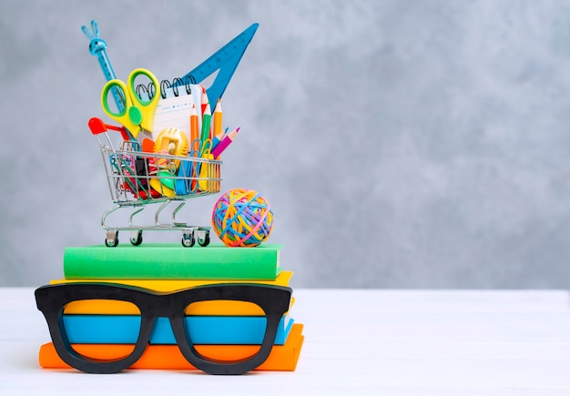 Material escolar colorido no cesto de compras com um espaço de texto de cópia.
