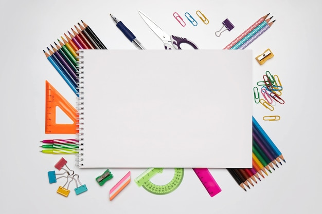 Material escolar colorido para aprendizagem em leigos planos e brancos