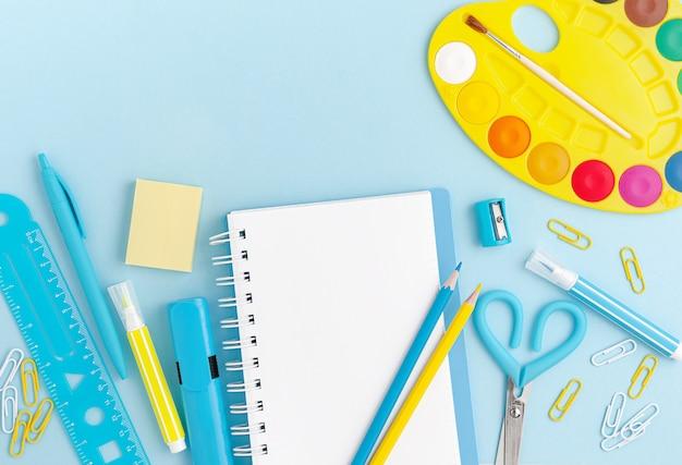 Material escolar colorido para crianças, nota em branco branca sobre fundo azul pastel. copie o espaço, vista superior.