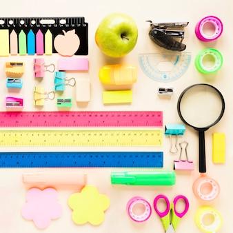 Material escolar colorido sobre fundo rosa claro