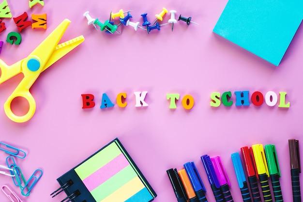Material escolar com canetas, tesoura, clipe de fichário, alfinetes, nota de papel e texto voltar a s