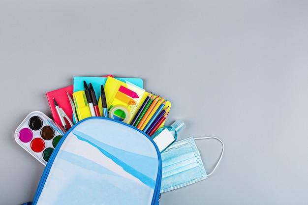 Material escolar com máscara protetora médica sobre um fundo cinza. proteção de escolares e estudantes do coronavírus covid-19, escolaridade em uma pandemia. postura plana, vista superior, maquete, modelo