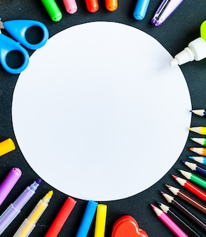 Material escolar com nota branca em branco ou fundo do cartão, vista superior