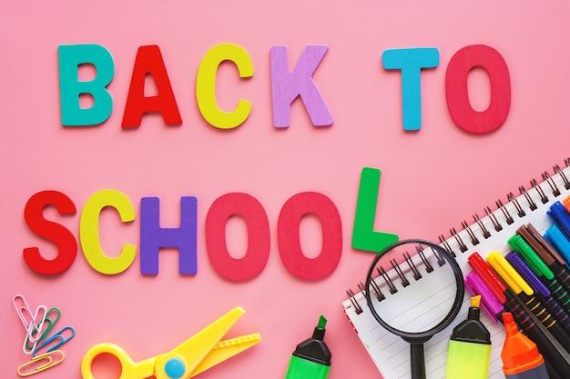 Material escolar com texto de madeira volta à escola no fundo rosa para o conceito de educação