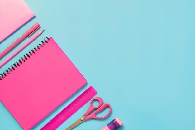 Material escolar cor-de-rosa, cadernos e penas no azul punchy. vista superior, lay plana. copie o espaço.