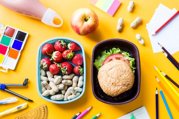 Material escolar da criança e almoço em caixas plásticas em um fundo amarelo