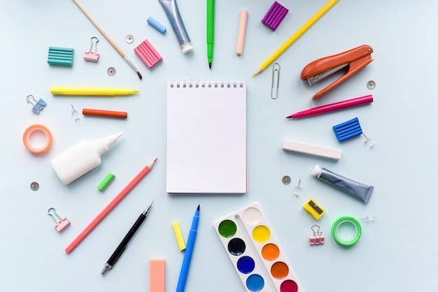 Material escolar diferente colorido em fundo de papel azul suave.