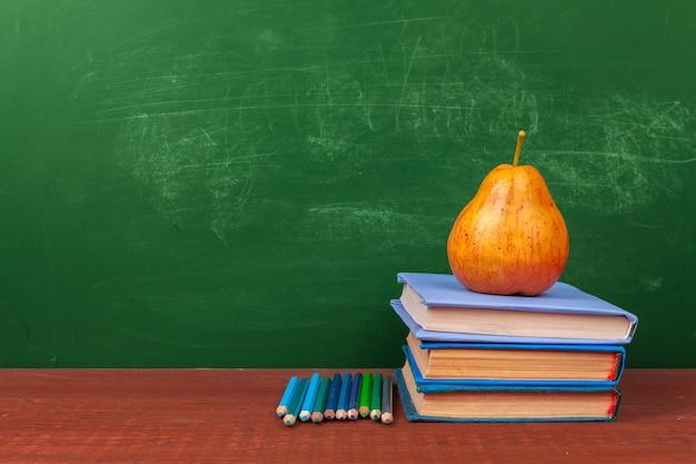 Material escolar diferente, livros e pêra na mesa de madeira