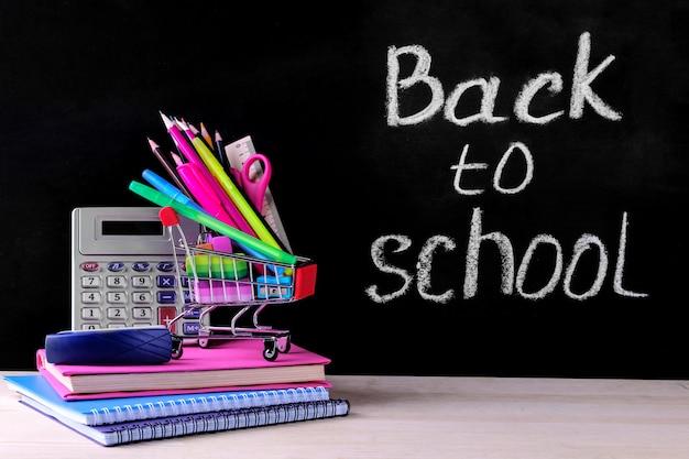 Material escolar e carrinho de compras no fundo do conselho escolar