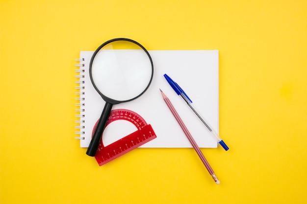 Material escolar e de escritório em fundo amarelo