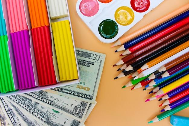 Material escolar e dólares, conceito é comprar objetos de papelaria.
