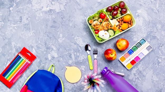Material escolar e lancheira com comida para crianças, copie o espaço