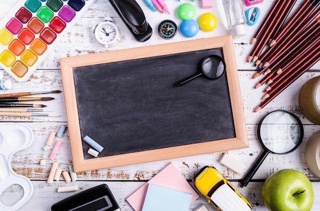Material escolar e quadro de giz na vista superior de madeira, plana leigos