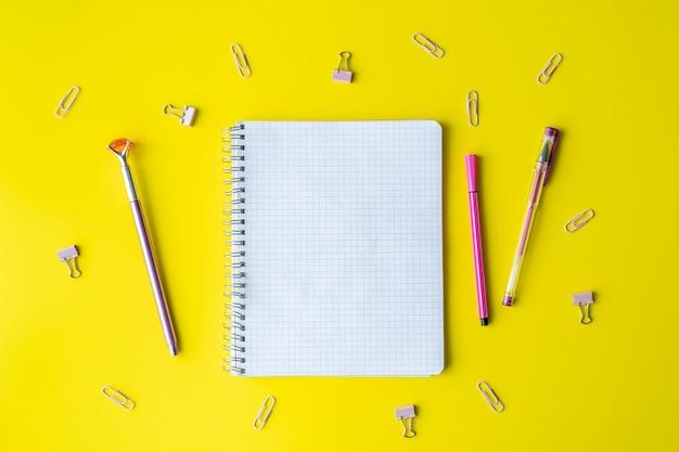 Material escolar e um caderno caem em amarelo