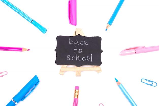Material escolar e um quadro negro com volta às aulas