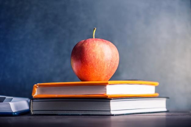 Material escolar em cima da mesa. livros e maçãs é uma coleção do aluno.