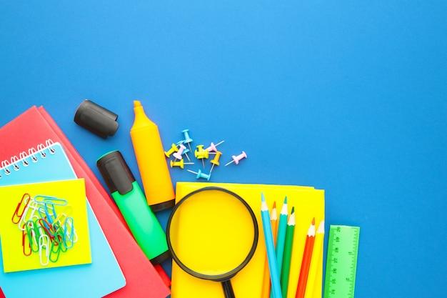 Material escolar em fundo azul. de volta à escola. postura plana.
