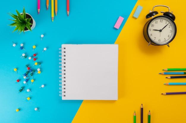 Material escolar em fundo azul e amarelo com lugar para texto.
