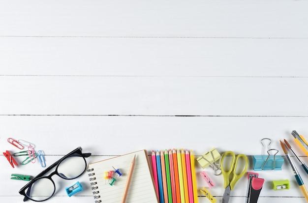 Material escolar em fundo branco de madeira com copyspace. educação ou de volta ao conceito de escola.