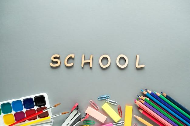 Material escolar em fundo cinza. vista superior, volta ao conceito de escola.