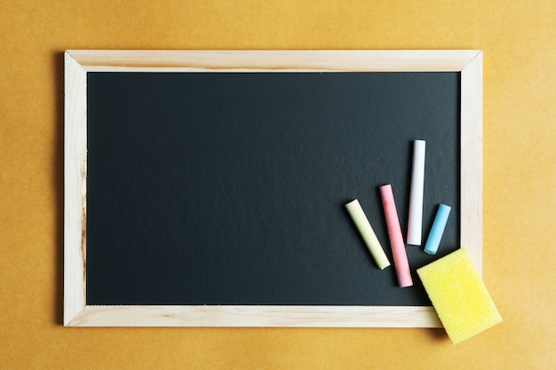 Material escolar em fundo de quadro negro. volta ao conceito de escola