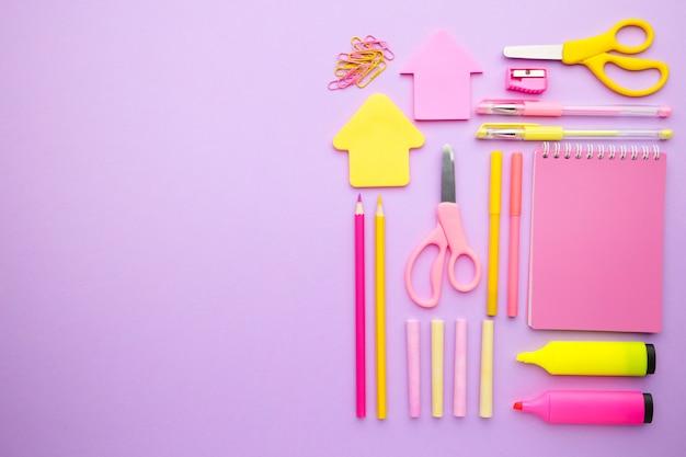 Material escolar em fundo rosa com espaço de cópia. de volta à escola. postura plana.