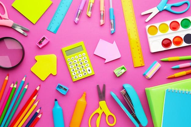 Material escolar em rosa com espaço de cópia.
