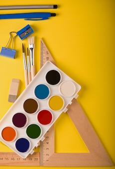 Material escolar em textura de fundo colorido abstrato.