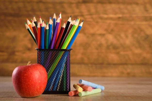 Material escolar em um fundo de madeira quente e bonito. lápis de cor infantil em um suporte de armário preto para artigos de papelaria.