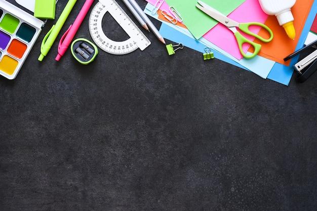 Material escolar em um fundo preto. de volta ao conceito de escola. composição plana leiga com artigos de papelaria da escola.