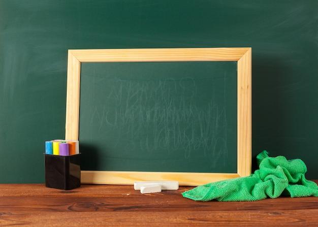 Material escolar em uma mesa de madeira e quadro-negro com copyspace