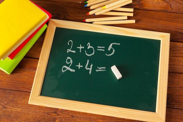 Material escolar em uma mesa de madeira e quadro-negro