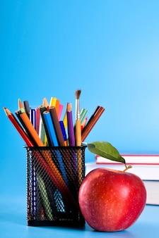Material escolar lápis, canetas, régua, pincel, livros e maçã azul