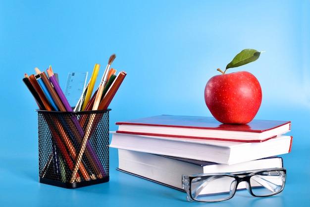 Material escolar lápis, canetas, régua, pincel, livros, óculos e maçã em uma parede azul com um lugar para texto