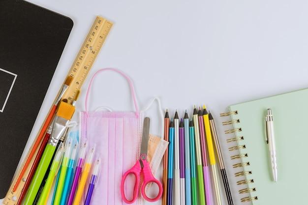 Material escolar, lápis de cor, ônibus escolar sobre uma pandemia segura de coronavírus covid-19