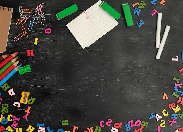 Material escolar: lápis de madeira multicoloridos, caderno, etiquetas de papel