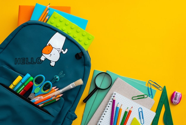 Material escolar, mochila azul, máscara médica, fundo amarelo, volta para a escola pandemia coronavírus con ...