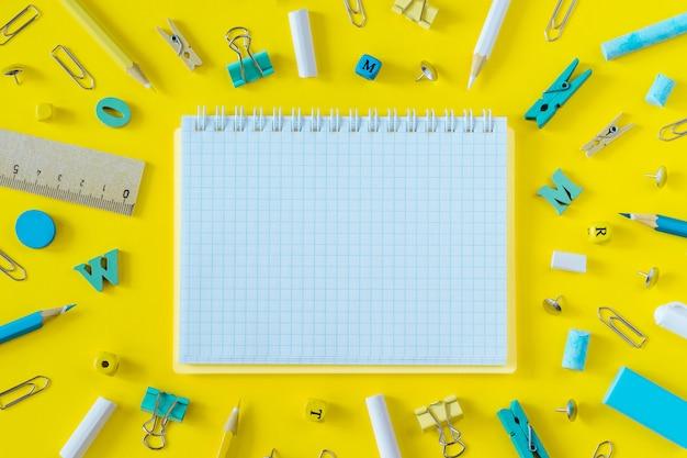 Material escolar multicolorido e plano de fundo do caderno em branco