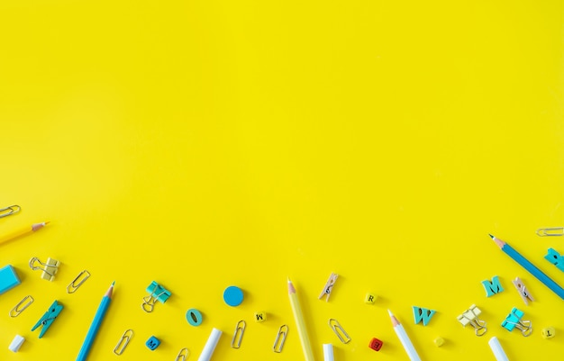 Material escolar multicolorido em fundo amarelo com espaço de cópia