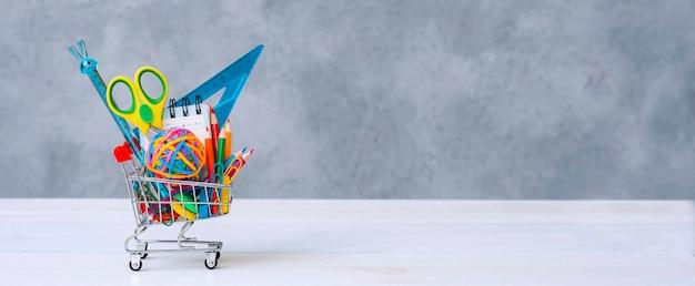 Material escolar multicolorido em um carrinho de compras em um fundo cinza com espaço de cópia para o texto