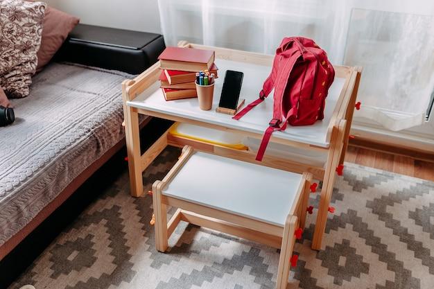 Material escolar na carteira da escola. mochila vermelha, fones de ouvido brancos, caderno, grandes livros vermelhos, canetas no frasco deitado sobre a mesa branca da escola.