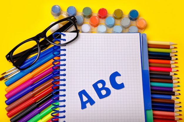 Material escolar na mesa amarela. plana. volta ao conceito de escola