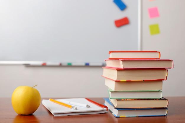 Material escolar na mesa da sala de aula na frente do quadro branco