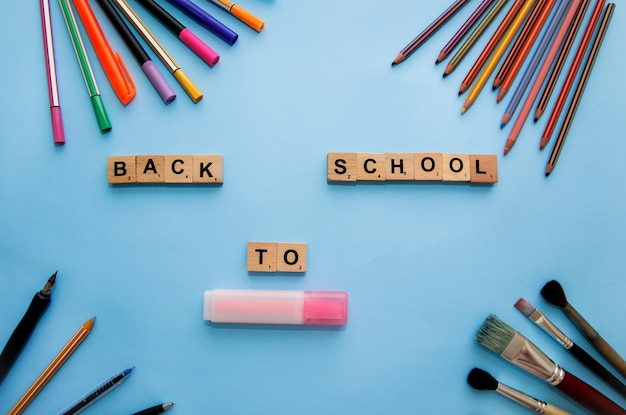 Material escolar na mesa. volta ao conceito de escola. quadro de material escolar. papelaria e cartas.