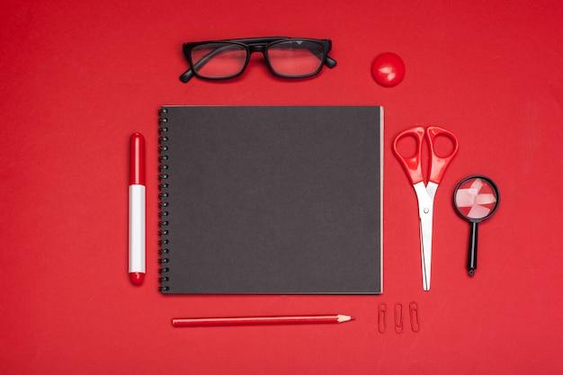 Material escolar na vista superior de mesa vermelha