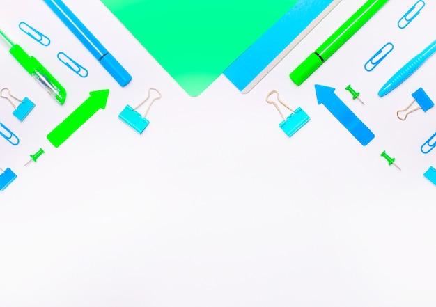 Material escolar nas cores azuis e verdes claras sobre um fundo claro com espaço de cópia. postura plana