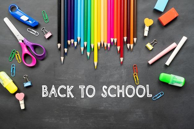 Material escolar no fundo do quadro negro. conceito de volta às aulas