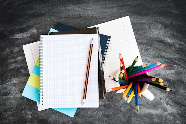 Material escolar no fundo do quadro negro. lápis de cor, calculadora, regras e cadernos. de volta ao conceito de escola.