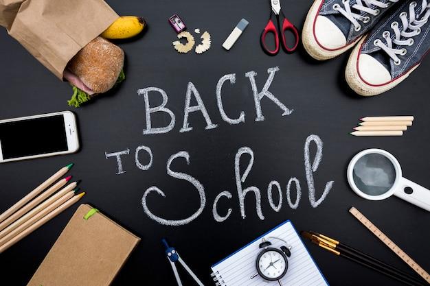 Material escolar no quadro-negro com a escrita